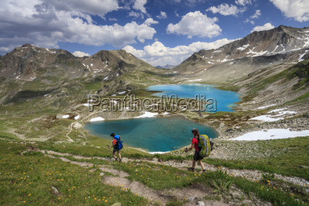 hikers pass the turquoise lake and