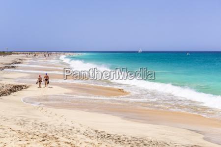 tourists walking along the sandy beach